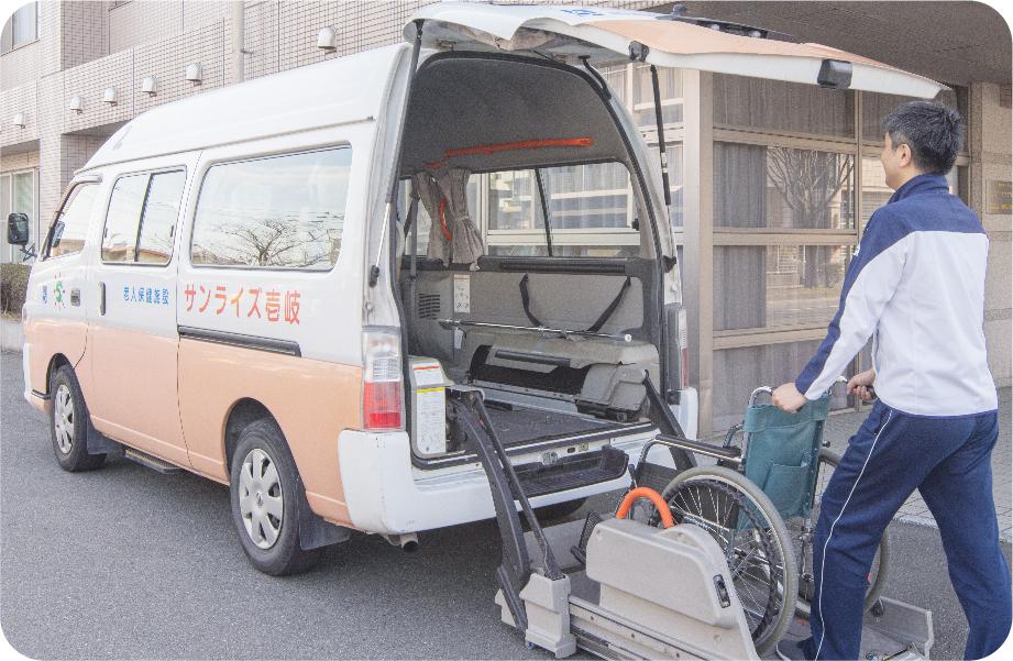 写真:送迎車に車椅子を積み込む男性スタッフ