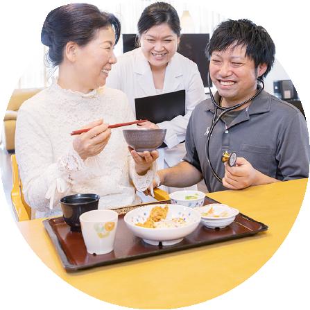 写真:食事中の女性利用者に声を掛ける男性スタッフ