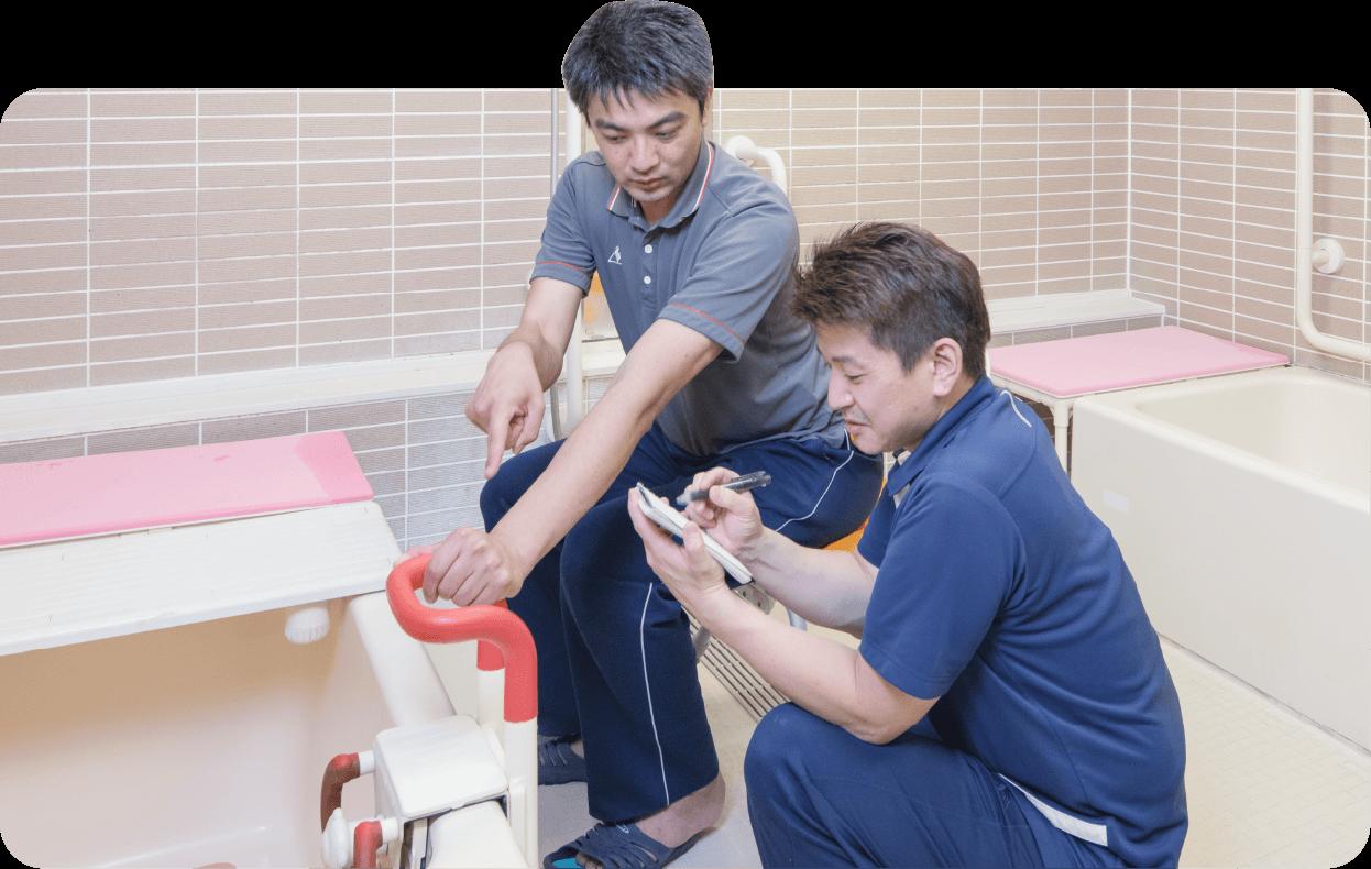 写真:お風呂で入浴介助の手順を確認中の男性スタッフ